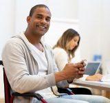 Man in wheelchair using smartphone at work