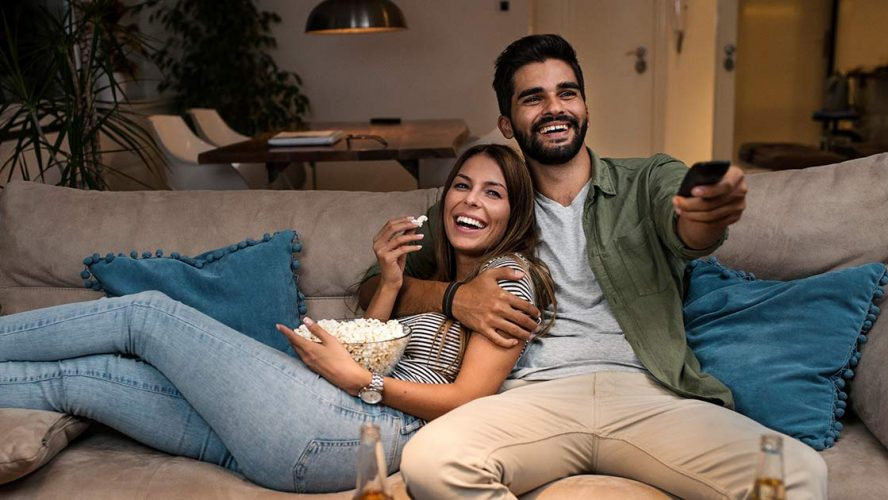 A couple having a movie night from their living room couch