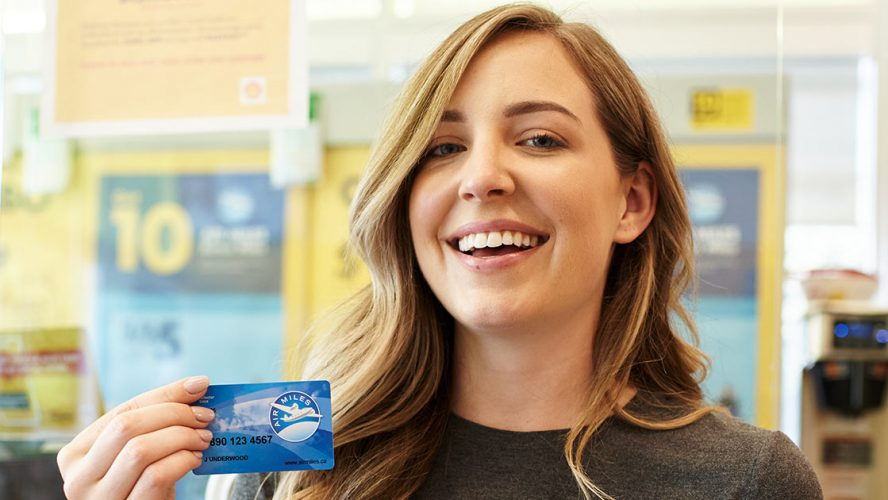Happy AIR MILES Collector showing off her AIR MILES card
