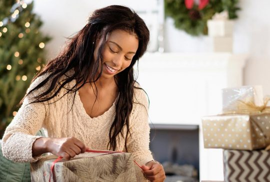 Woman tying a bow on a wrapped holiday gift