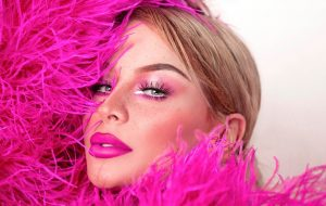 Close-up of Gigi Gorgeous in a hot pink feather boa outfit