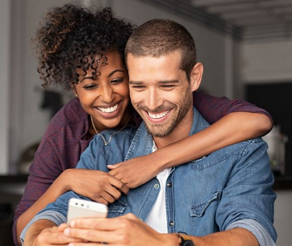 Couple happily browsing a smartphone together