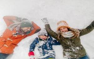 Family of Three Playing in Snow