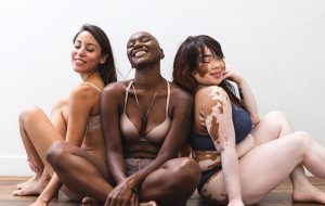 Three models smiling and sitting on the floor together