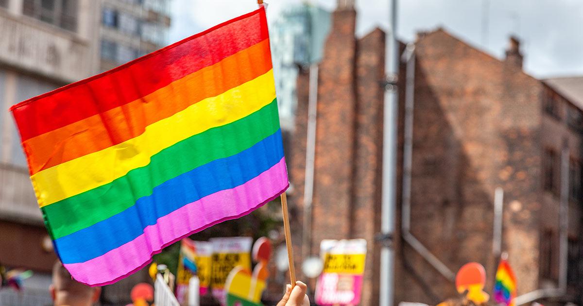 Waving a rainbow flag at a Pride Parade