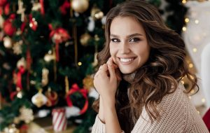 Woman smiling in front of a Christmas tree