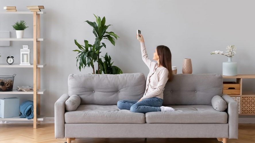 Woman using ventilation remote control in her house