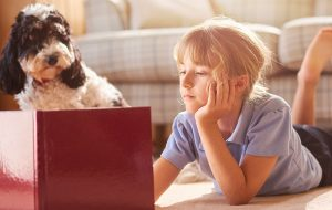 Young girl and her dog reading a book