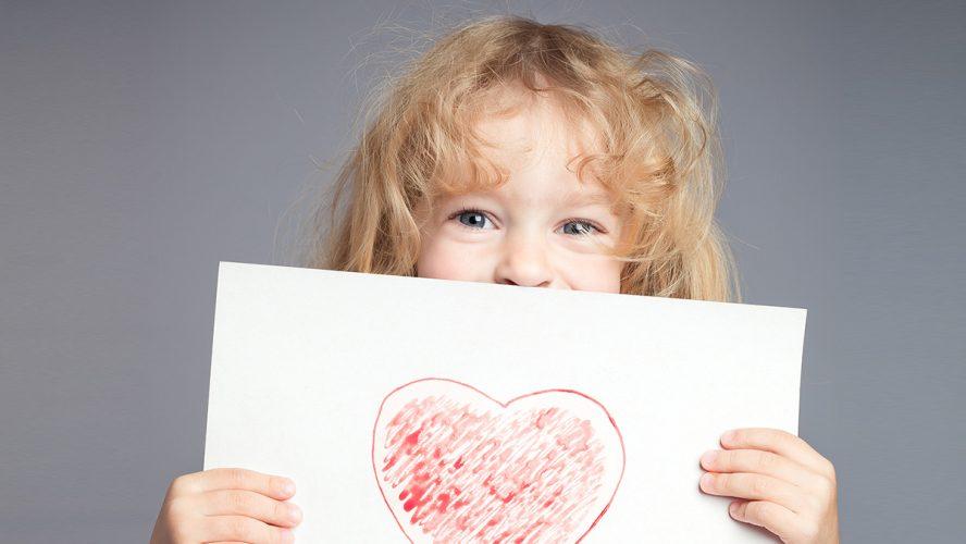dziecko trzymające w dłoniach kartę z narysowanym sercem