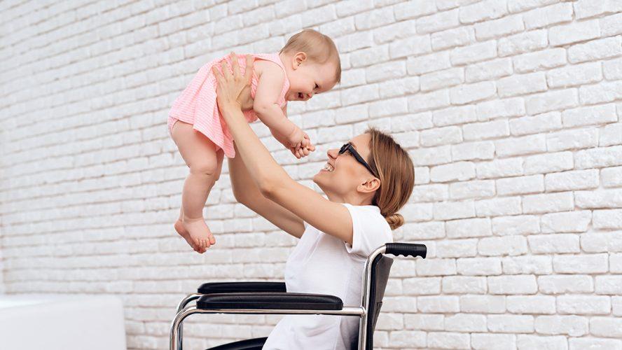 kobieta na wózku inwalidzkim trzymająca niemowlę w ramionach