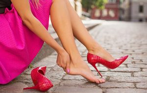 kobieta z bolącymi stopami zdejmująca szpilki