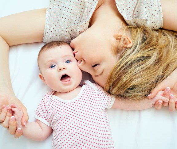 młoda mama całująca swoje niemowlę na łóżku