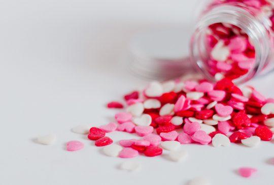 przewrócony flakonik z małymi tabletkami w kształcie serduszek