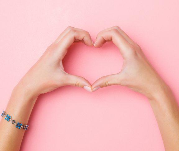 ręce złożone w serce na różowym tle