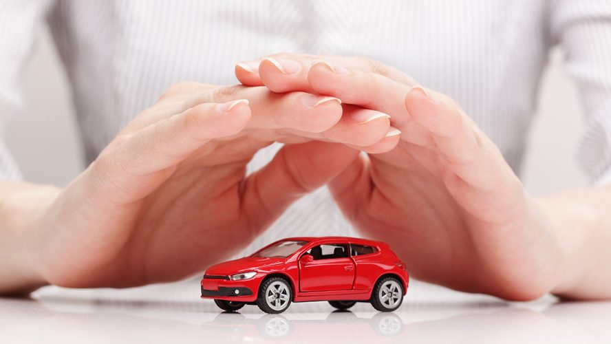 dłonie ułożone w geście ochronnym nad małym modelem samochodu