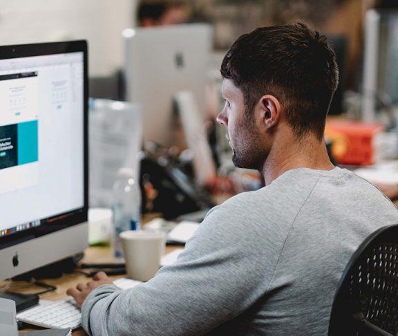Mann foran dataskjerm på jobb