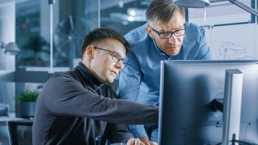 To menn ser på dataskjerm
