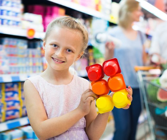 Jente holder opp youghurtbeger i butikk
