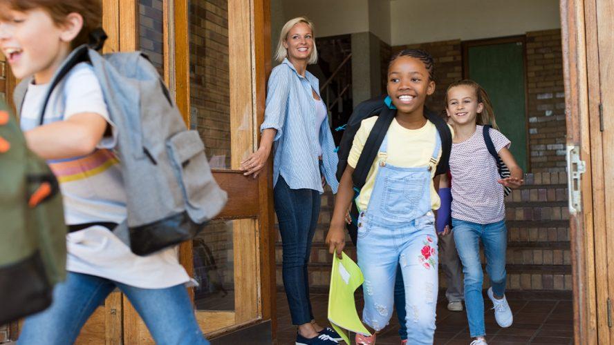 Skolebarn løper ut døra