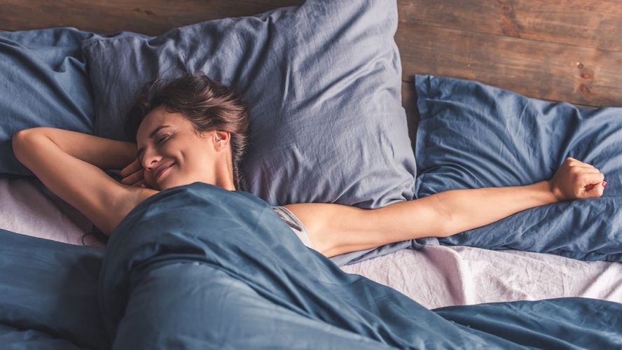 Jente som strekker seg i senga