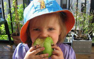Liten jente med solhatt og eple i munnen