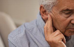 ældre mand sidder og holder sig til øret som om han har høretab