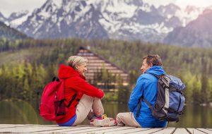 to rejsende sidder på kanten til en sø med bjerge i baggrunden