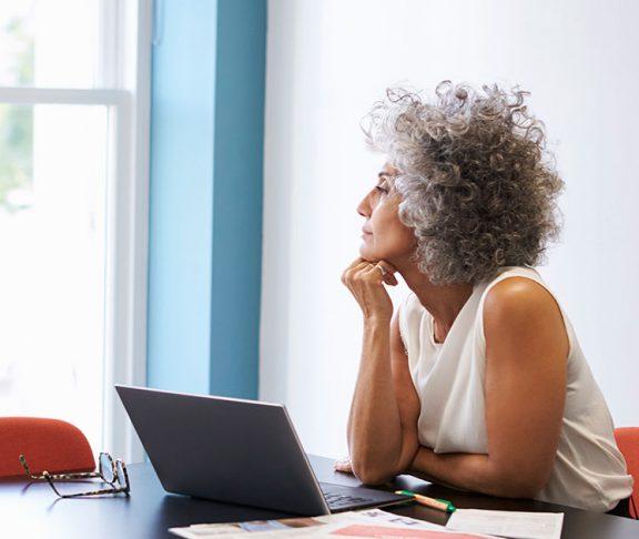 Moden kvinde sidder foran computer og stirre ud ad vinduet