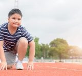 Overvægtig dreng klar til at løbe på stadion