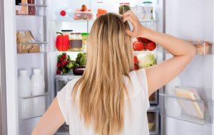 Kvinde kigger ind i sit køleskab og finder madvarer hun ikke behøver have der