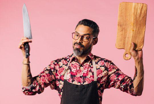 Hjemmekok i forklæde med kniv og skærebræt