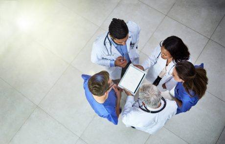 High angle shot of a diverse team of doctors using a digital tablet together