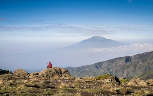 Man siting with his phone with view on Mount Meru, Tanzania