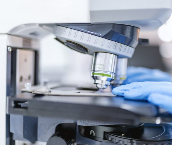 Close-up of scientist hands with microscope, examining samples and liquid. Men in a laboratory microscope with microscope slide in hand. Scientific and healthcare research background