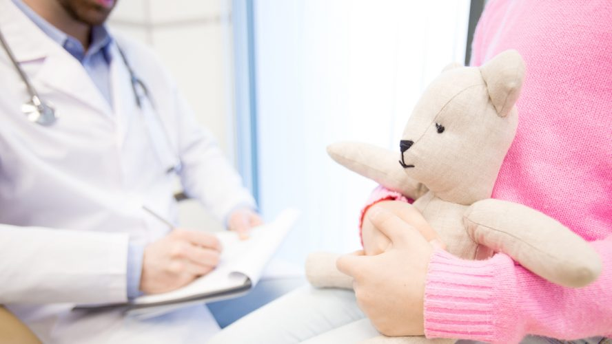 White teddybear in hands of little patient waiting for her doctor making prescriptions