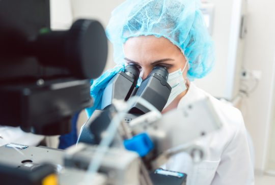 Woman scientist working on microscope in laboratory