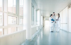 Three doctors on hospital corridor having short meeting discussing some cases