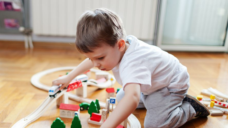 Little boy playing with wooden train set