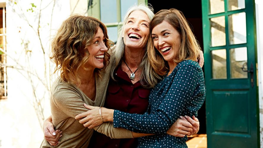 Mother and daughters embracing outdoors
