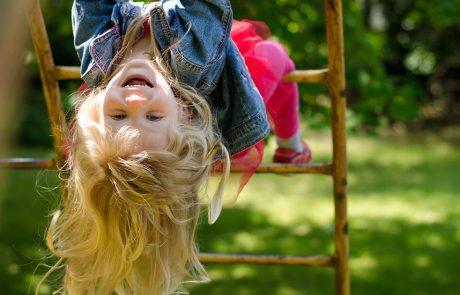 Pige hænger på hovedet på legeplads