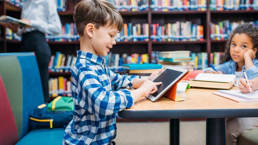 Dreng leger med iPad på skolebiblioteket