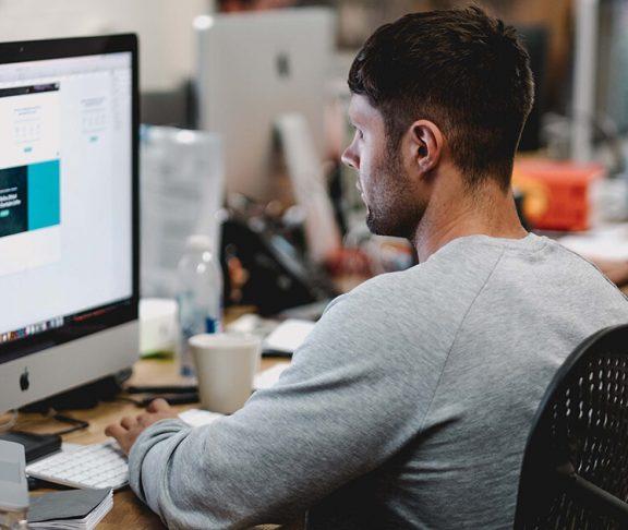 praktikant sidder foran computeren på arbejdsplads