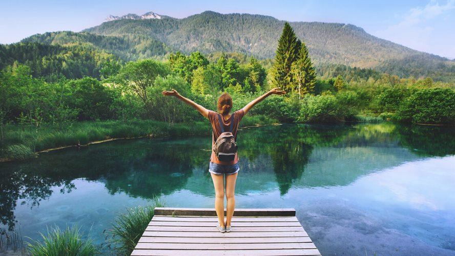 Kvinde står med ryggen til på badebro ved smuk sø