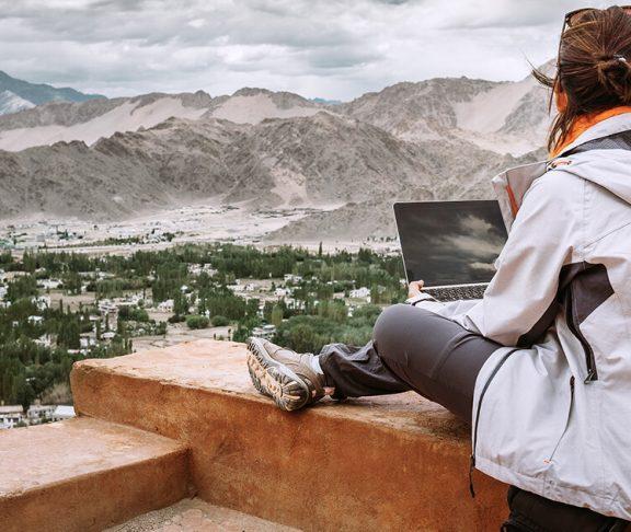 kvinde der er i udlands praktik sidder og kigger ud på bjerge med sin computer i skødet
