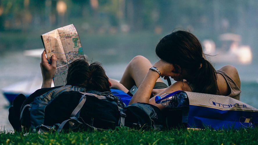 Par ligger i græsset sammen og læser