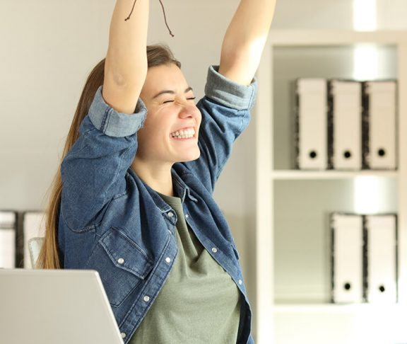 Ung kvinde rækker sejrrigt armene i vejret