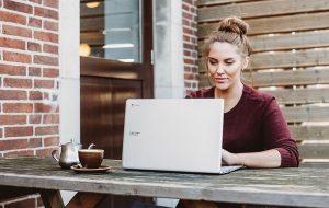 Ung kvinde sidder ved havebord med laptop