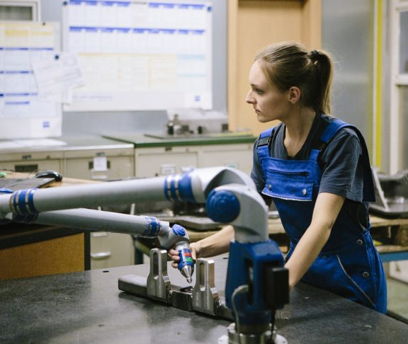 young female trainee makes an quality control with a coordinate measuring machine (3D-romer arm) in a metal manufacturing company