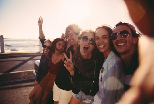Group of hipster friends cheering and showing peace sign while taking a self portrait close to the beach on a summer afternoon