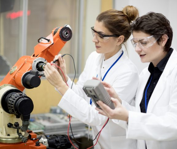 Female engineers repairing electronic machine